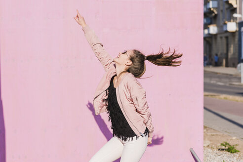 Happy young woman moving in front of pink wall - UUF15701