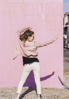 Happy young woman moving in front of pink wall - UUF15704