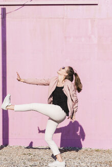 Happy young woman moving in front of pink wall - UUF15707