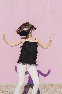Young woman wearing VR glasses moving in front of pink wall - UUF15713