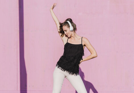 Happy young woman wearing headphones dancing in front of pink wall - UUF15719