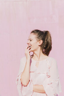 Laughing young woman in front of pink wall - UUF15734