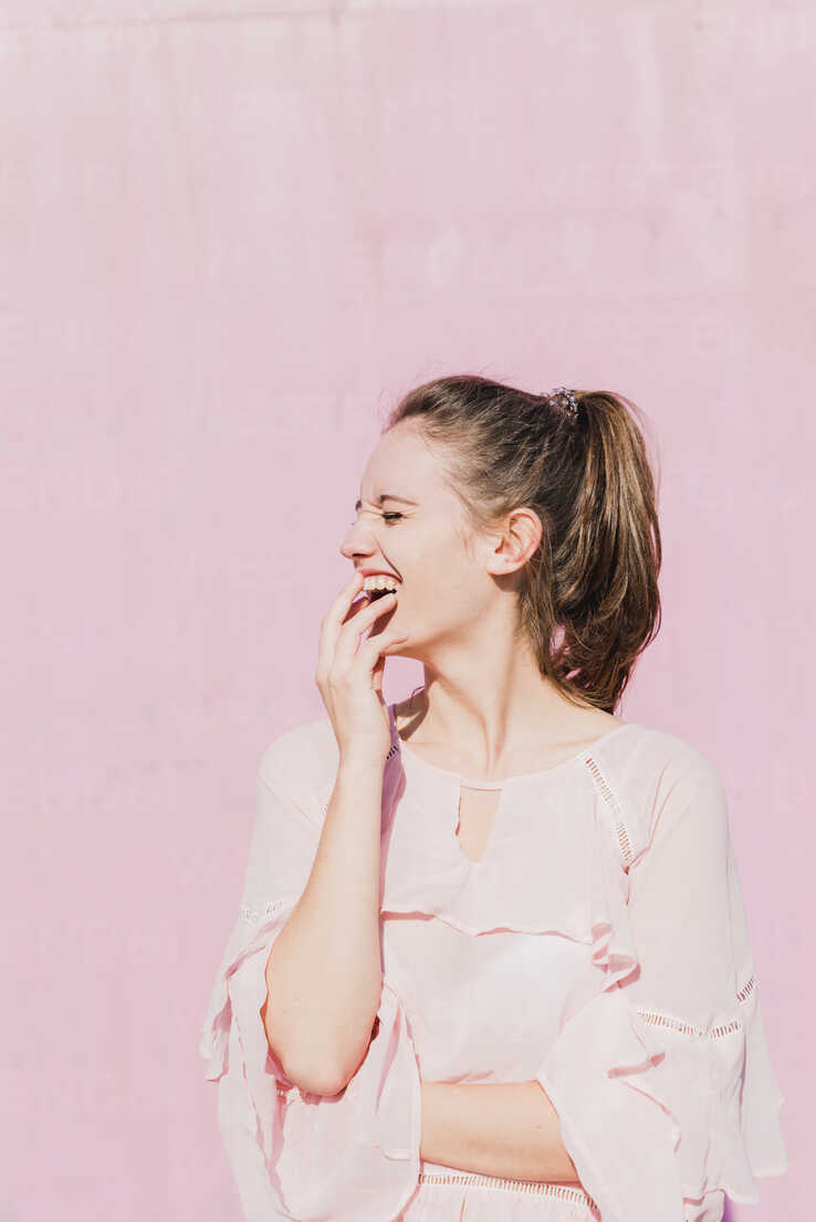 Laughing young woman in front of pink wall - UUF15734 - Uwe Umstätter/Westend61