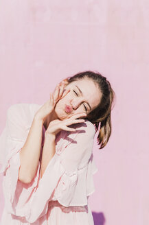 Portrait of young woman grimacing in front of pink wall - UUF15737