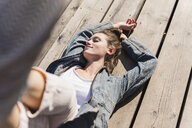Relaxed young woman lying on wooden boards in sunshine - UUF15746