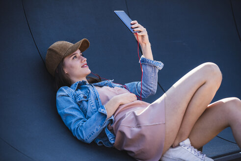 Young woman lying outdoors holding cell phone - UUF15755