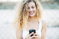 Portrait of laughing blond young woman looking at mobile phone - OCMF00014