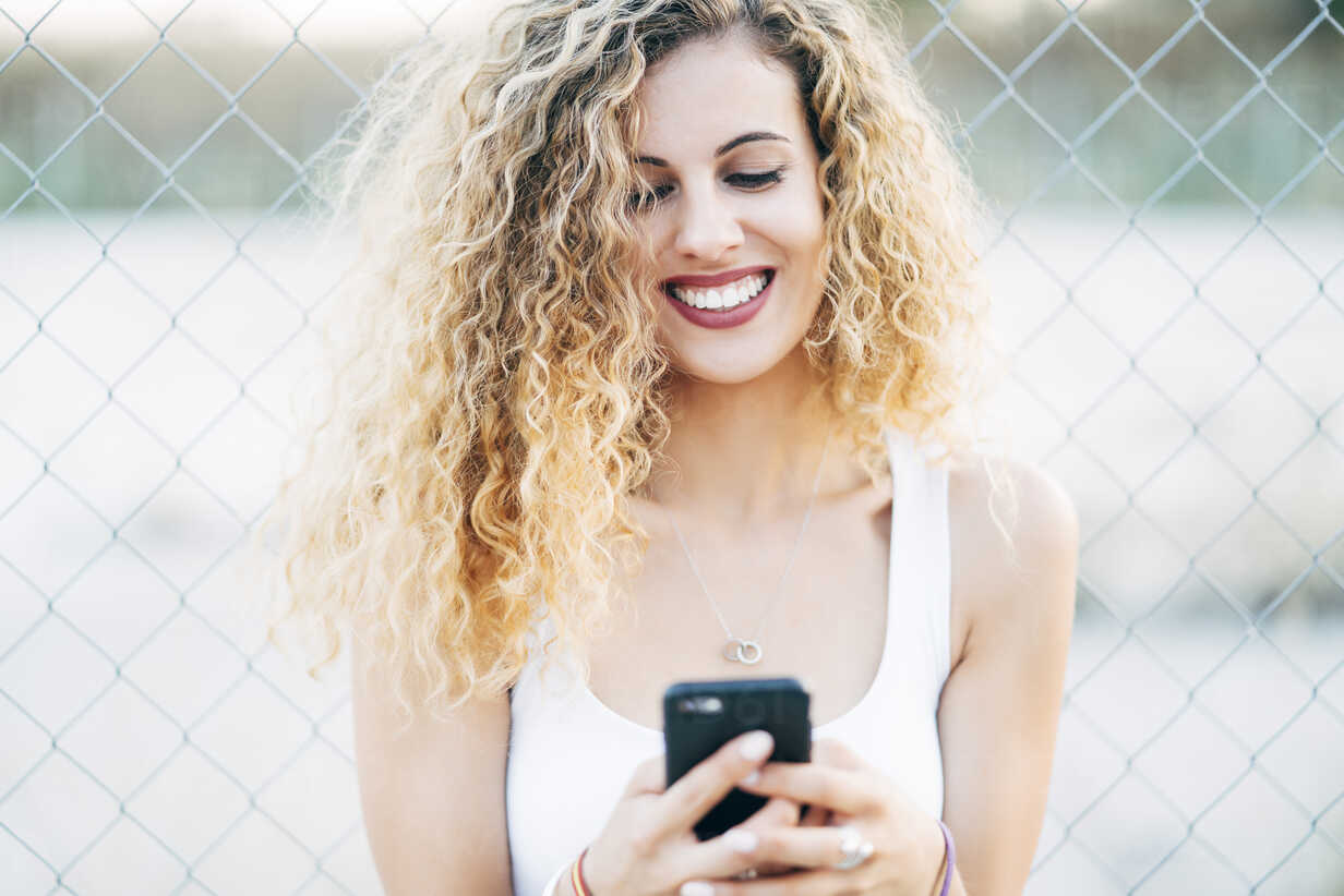 Portrait of laughing blond young woman looking at mobile phone - OCMF00014 - Oscar Carrascosa Martinez/Westend61