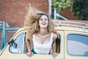 Portrait of blond woman leaning out of window of classic car tossing her hair - OCMF00026