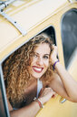 Portrait of happy blond woman looking out of window of classic car - OCMF00032