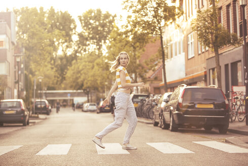 Young woman walking on zebra crossing - JESF00191