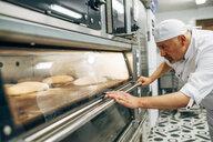 Working baker preparing the oven to make bread - OCMF00041