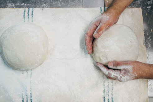 Baker working with dough in bakery - OCMF00044