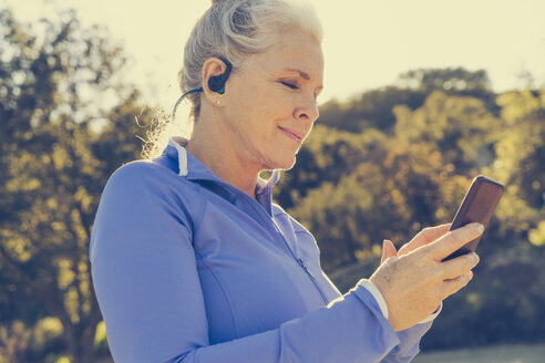 Mature woman in sportswear listening to music on earphones using smart phone - TGBF00847