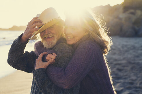 Side view of happy mature couple embracing on beach at sunset - TGBF00859