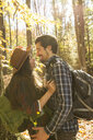 Side view of romantic male and female backpackers looking at each other in forest during autumn - TGBF00895