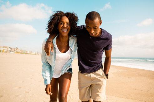 Couple walking on beach on sunny day - TGBF00901
