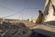 Side view of thoughtful woman sitting on deck of sailboat - TGBF00910