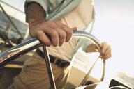 Close up of man steering sailboat - TGBF00913