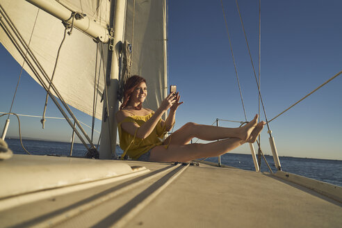 Happy woman photographing through smart phone while sitting on sailboat - TGBF00916
