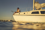 Romantic couple sitting on sailboat deck  during sunset - TGBF00922
