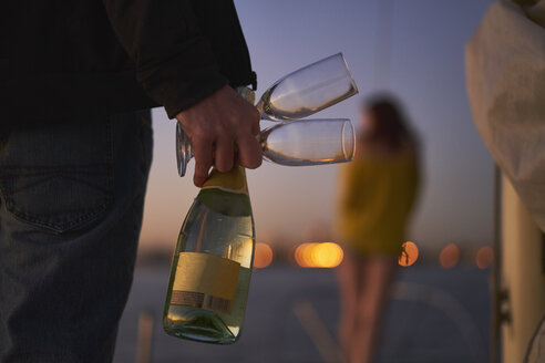 Rear view of man holding champagne flutes and bottle on sailboat while woman standing in background at dusk - TGBF00928
