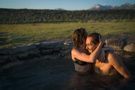 Woman Embracing Smiling Boyfriend In Hot Spring - TGBF00940