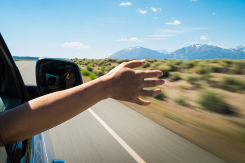 Woman holding hand out car window on road trip - TGBF00961