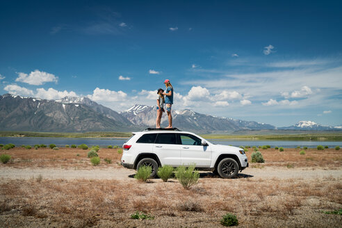 Couple Standing On Car Against Mountains - TGBF00964