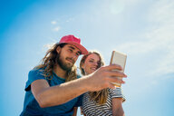 Couple Taking Selfie On Smartphone Against Sky During Summer - TGBF00967