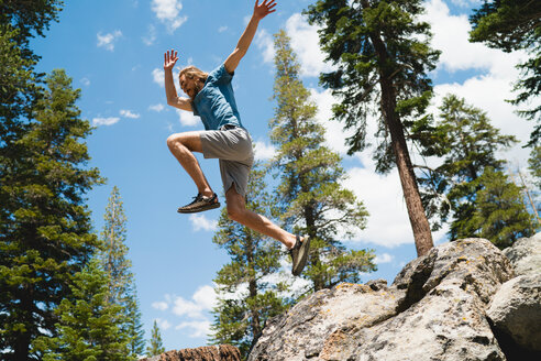 Male Hiker Jumping In Forest - TGBF00973