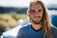 Man With Long Blond Hair Smiling On Sunny Day - TGBF00976