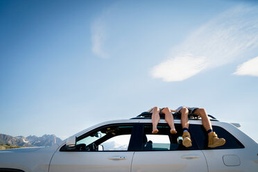 Low Section Of Couple Lying On Car Roof - TGBF00979