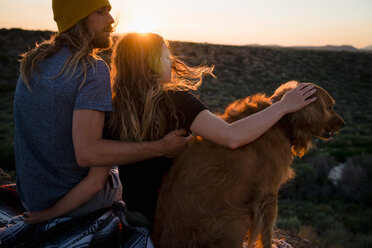 Hikers With Dog Sitting On Mountain During Sunset - TGBF00985