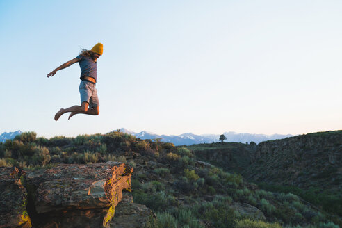 Hiker Jumping On Mountain Against Sky - TGBF00988