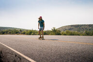 Man skateboarding on empty road against sky - TGBF00997