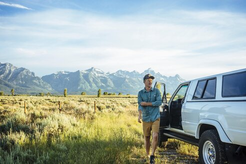 Young man walking by car with mountains in background at Grand Teton National Park - TGBF01006