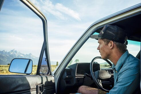 Young man sitting in car with open door at Grand Teton National Park - TGBF01009