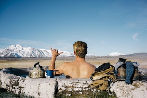 Rear view of shirtless young man gesturing while relaxing in natural thermal hot spring near Mammoth Lakes - TGBF01012