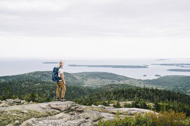 Full length of backpacker looking at ocean view from mountain at Acadia National Park - TGBF01033