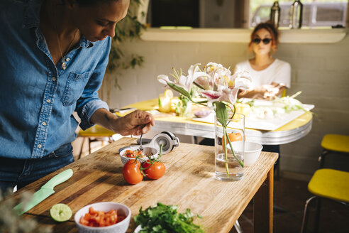 Mid adult woman preparing Mexican salsa at wooden table with friend in background at home - TGBF01060