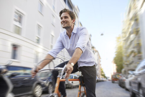 Smiling young man riding racing cycle in the city - PNEF01081