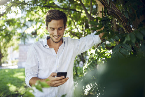 Portrait of smiling young man in  a park looking at cell phone - PNEF01093