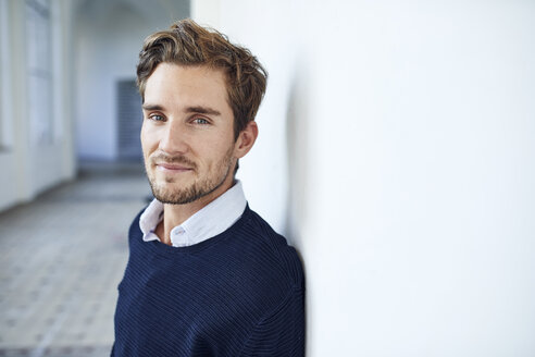 Portrait of smiling young man leaning against wall - PNEF01099