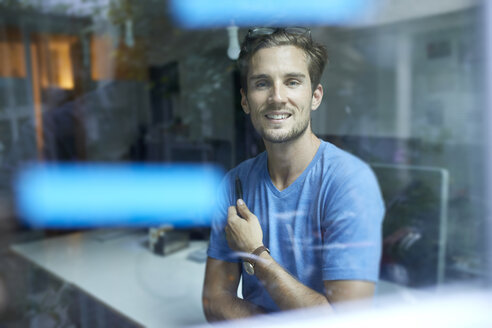 Portrait of content young man behind windowpane in an office - PNEF01108