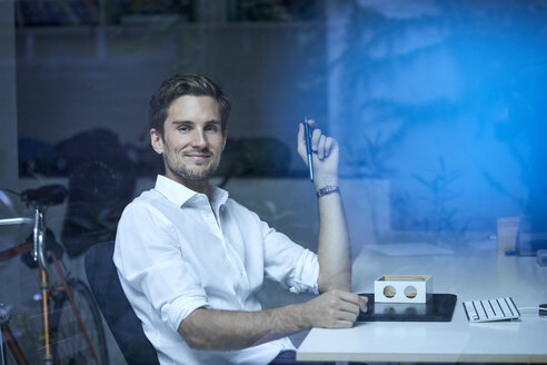 Portrait of smiling young man behind windowpane at his office desk - PNEF01114