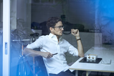 Pensive young man behind windowpane sitting at office desk looking at prototype - PNEF01117
