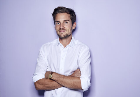 Portrait of content young businessman in front of purple background - PNEF01123