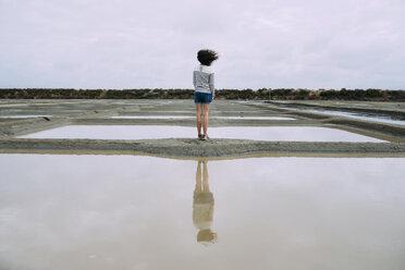 France, Bretagne, Woman surrounded by salt ponds in Marais salants de Guerande - GEMF02444