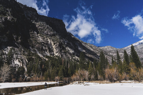Hiker standing by river on snow against mountains at Yosemite National Park during winter - CAVF52351